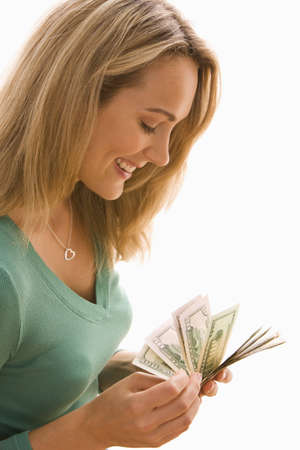 wealthy: An attractive young woman is counting through a selection of paper bills.  Vertical shot.