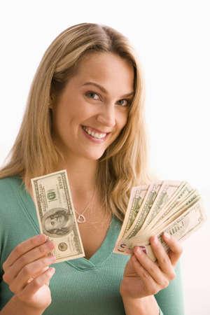 Attraktive junge Frau zeigt eine Auswahl an Geld, die Sie h�lt. Vertikal gedreht.