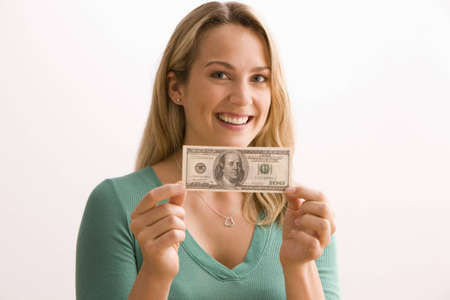 An attractive young woman is holding up a $100.00 bill and smiling at the camera.  Horizontal shot. Stock Photo