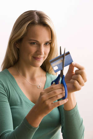 to cut: A young woman is cutting through her credit card with scissors.  Vertical shot.