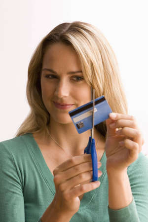 A young woman is cutting through her credit card with scissors.  Vertical shot.