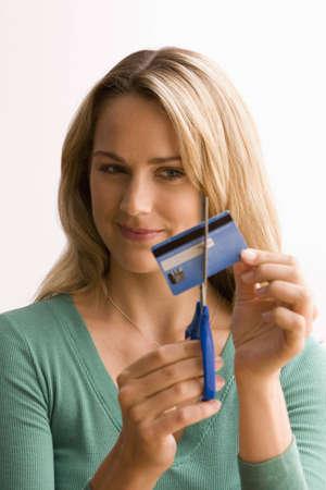 Eine junge Frau ist durch Ihre Kreditkarte mit einer Schere schneiden. Vertikal gedreht.  Lizenzfreie Bilder