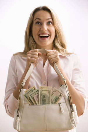 A young woman is holding a cash filled purse with large smile on her face.  Vertical shot.