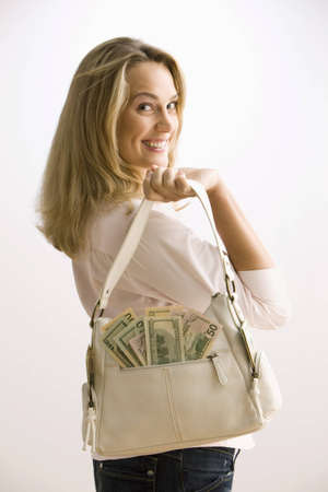 A young woman is holding a cash filled purse with large smile on her face.  Vertical shot. photo