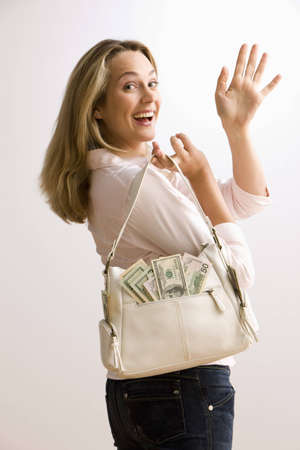 A young woman is holding a cash filled purse and waves back over her shoulder.  Vertical shot. Stock Photo