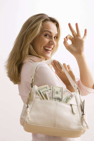 A young woman is holding a cash filled purse and gives the OK sign over her shoulder.  Vertical shot.