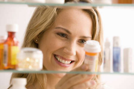 medicine cabinet: A young woman is looking through her medicine cabinet and smiling.  Horizontal shot. Stock Photo