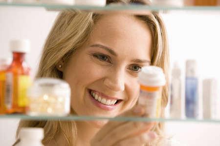Eine junge Frau ist der Blick durch Ihr Medizin-Kabinett und l�chelnd. Horizontale erschossen.