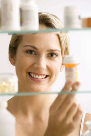 A young woman looks through a medicine cabinet and smiles at the camera.  Vertical shot. photo