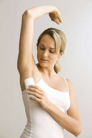 A young woman raises her arm up to apply deodorant.  Vertical shot. Stock Photo