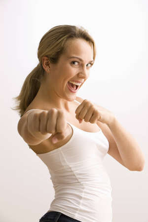 A young woman is playfully standing with her arm out in a punch.  She is smiling at the camera.   Horizontal shot.