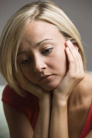 Ein junger wiegen Ihren Kopf in ihr H�nde mit einem traurigen Ausdruck auf Ihrem Gesicht. Vertikal gedreht.