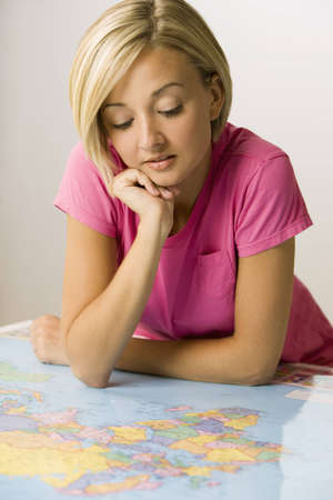 A young woman is leaning over a map and studying it.  Vertical shot. Stock Photo