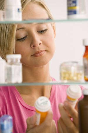 medicamentos: Una mujer joven est� leyendo las etiquetas de contenedores de medicina de su gabinete de medicina. Un disparo vertical.