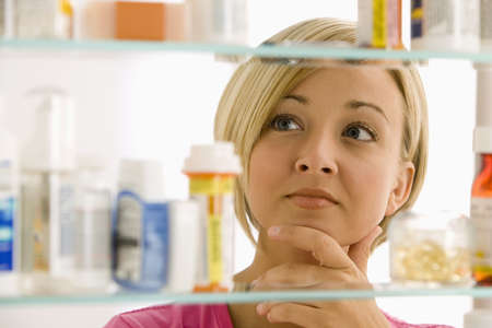 cupboard: A young woman is looking through her medicine cabinet.  Horizontal shot.