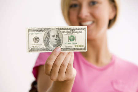 A young woman is holding out a $100.00 bill and smiling at the camera.  Horizontal shot. Stock Photo