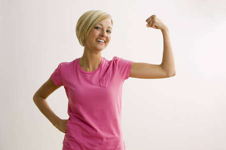 A young woman is flexing her bicep and smiling at the camera.  Horizontal shot. Stock Photo