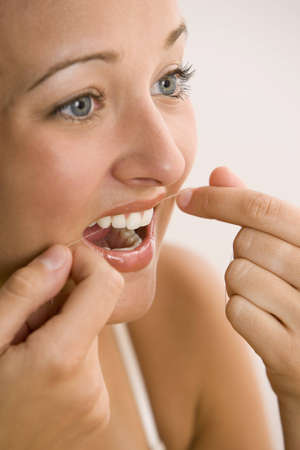 A young woman is flossing her teeth while looking to the side.  Vertical shot.
