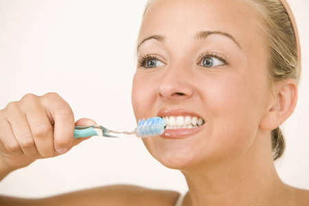 A young woman looks to the side while brushing her teeth.  Horizontal shot.