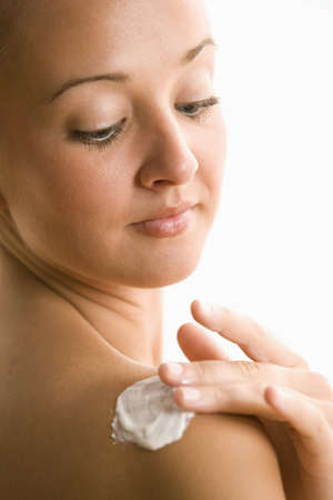 A young woman is rubbing lotion into her shoulder.  Vertical shot. photo