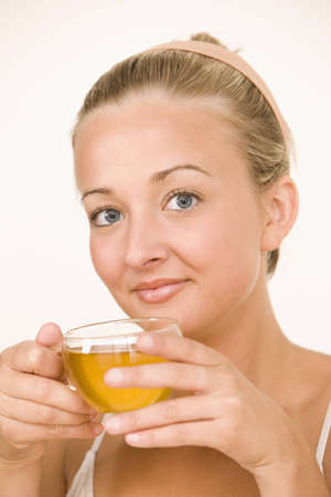 A young woman is drinking tea and smiling at the camera.  Vertical shot. Stock Photo - 7466812