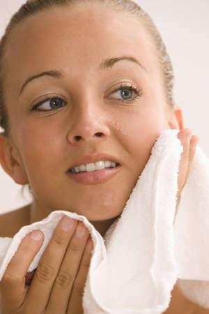 Eine junge Frau ist Ihre Haut mit einem Handtuch trocknen, nach dem Waschen Sie Ihr Gesicht. Vertikal gedreht.