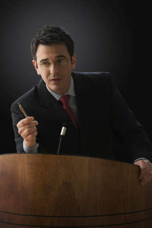 A businessman is standing at a lectern with a microphone giving a lecture. He has a pen in his hand and is gesturing with it. Vertical shot.