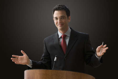 A businessman is standing at a podium with a microphone giving a lecture with outstretched hands. Horizontal shot. Stock Photo