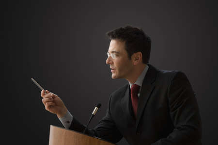 A businessman is standing at a podium with a microphone giving a lecture.  He has a pen in his hand and is gesturing with it. Horizontal shot.