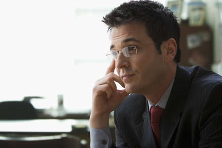 A young businessman wearing glasses is sitting in an office with his hand to his head. Horizontal shot.