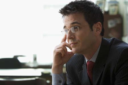 A young Businessman wearing Glasses sitzt in einem B�ro mit seiner Hand auf dem Kopf. Horizontale erschossen. Lizenzfreie Bilder