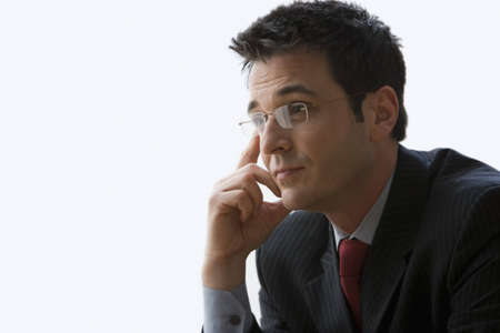 A young businessman wearing glasses is sitting with his hand to his head. Horizontal shot. Isolated on white.
