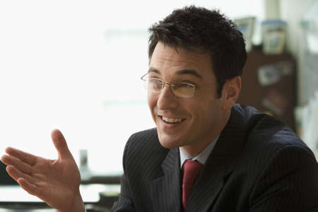 A businessman smiling and wearing glasses is sitting in his office talking to someone off camera. Horizontal shot.