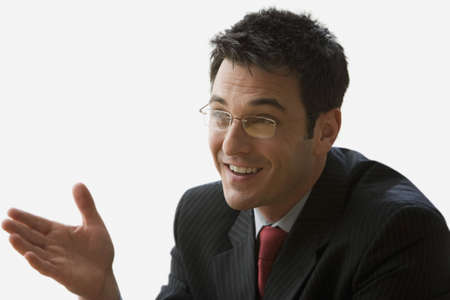 A businessman smiling and wearing glasses is sitting in his office talking to someone off camera. Horizontal shot. Isolated on white. Stock Photo