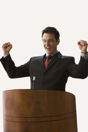 A young businessman is standing at a podium with fists raised. Vertical shot. Isolated on white.