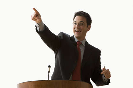 A young businessman is standing at a podium and pointing. Horizontal shot. Isolated on white. Stock Photo