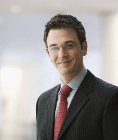 thirties portrait: A handsome young businessman wearing glasses and smiling. Vertical shot. Stock Photo