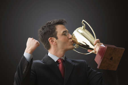 A businessman wearing glasses is holding a trophy and kissing it. Horizontal shot. Foto de archivo