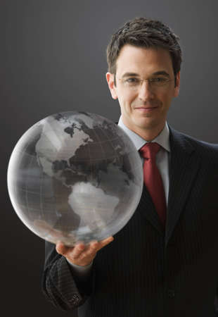 A handsome businessman is smiling at the camera while holding a clear globe. Vertical shot.