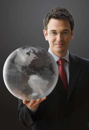 Ein gut aussehend Kaufmann ist an die Kamera l�chelnd, halten einen klaren Globus. Vertikal gedreht.