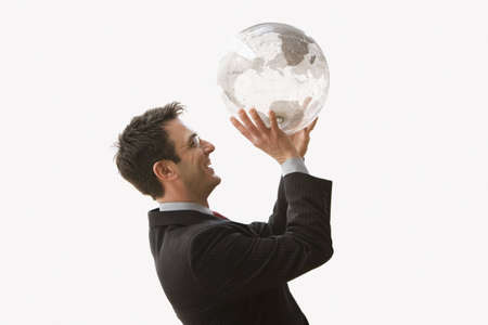 man side view: A businessman is smiling and wearing glasses while standing and holding a clear globe like he is shooting a basketball. Horizontal shot. Isolated on white.