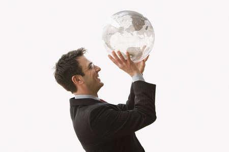 eye ball: Un hombre de negocios est� sonriendo y usan gafas mientras permanente y la celebraci�n de un globo claro como �l es rodar una pelota de baloncesto. Horizontal a tiros. Aislados en blanco.