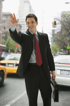 A businessman holding a briefcase is smiling and hailing a taxi. Vertical shot.