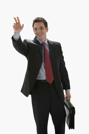 A businessman holding a briefcase is smiling and hailing a taxi. Vertical shot. Isolated on White. Stock Photo