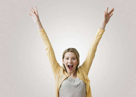 A young, excited woman has her arms outstretched in the air as she smiles at the camera.  Horizontal shot.