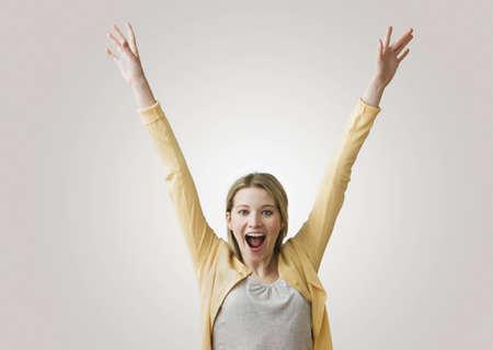 Eine junge, excited Frau hat ihre Arme ausgestreckt in der Luft, wie Sie in die Kamera l�chelt.  Horizontal gedreht.