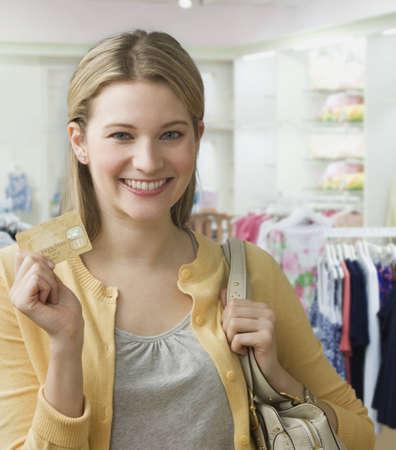 Eine junge Frau ist, h�lt eine Kreditkarte und l�chelt in die Kamera.  Sie steht in einem Bekleidungsgesch�ft.  Vertikal gedreht. Lizenzfreie Bilder