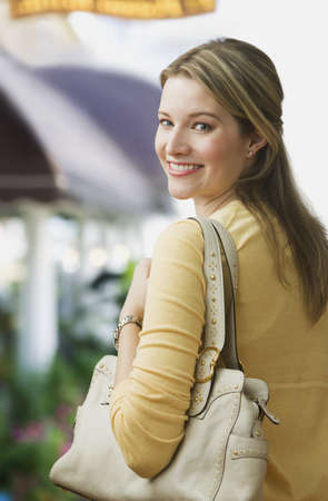 A young woman is smiling over her shoulder at the camera and is carrying a purse.  Vertical shot.