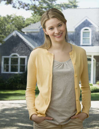 A young woman is standing outside in a residential neighborhood and smiling at the camera.  Vertical shot. Stock Photo