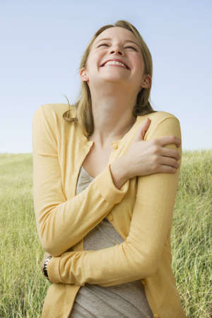 A beautiful young woman stands in a grass field while laughing.  Vertical shot. Stock Photo